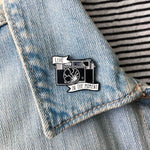 A broken camera brooch on the lapel of a denim jacket.