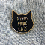 "A funny enamel pin for cat lovers and owners. Features a cat's head in black and gold with the quote, ""Needs More Cats""."