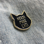 "A cute black and gold lapel accessory of a cat's head with the saying, ""Needs More Cats""."