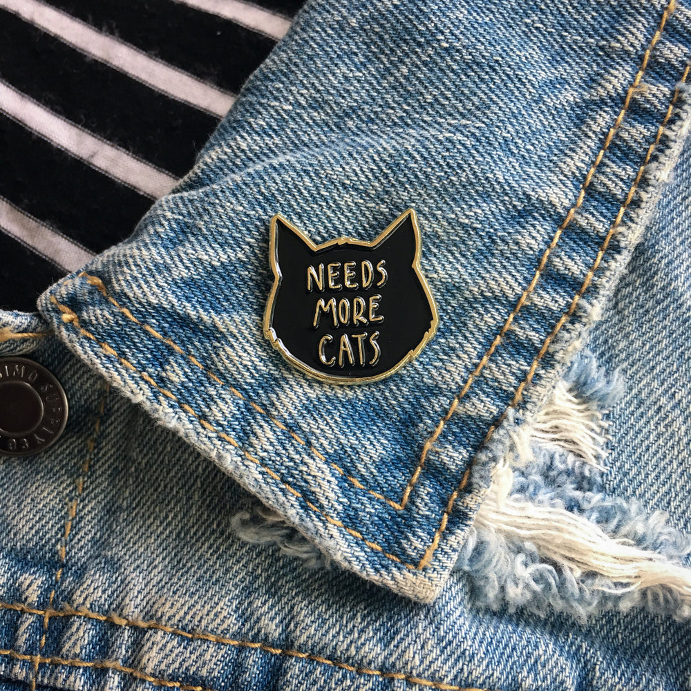 "Ectogasm's cute, ""Needs More Cats"" enamel pin on the lapel of a denim jacket for quirky fashion."
