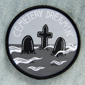 A round black, gray, and white patch of a graveyard with a funny quote.