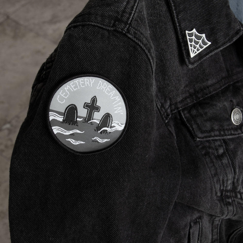 A patch of spooky headstones ironed onto a black denim jacket for punk fashion.