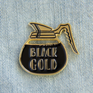 "A stylish enamel pin of a coffee pot with the quote, ""Black Gold""."