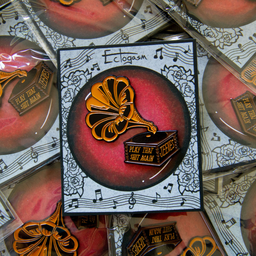 A phonograph lapel pin accessory on a music themed art card.