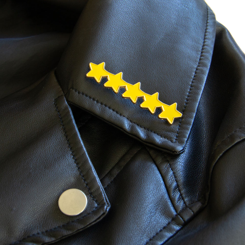 An enamel pin of 5 gold stars on a leather jacket for unisex street style as an employee of the month gift.