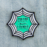 "A spooky enamel pin of a cobweb with the quote, ""Creepy But Lovable"" in the center for goth fashion."