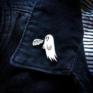 A sexy horror themed enamel pin of a ghost for nu goth and alternative fashion. Pictured on a black denim jacket's lapel.