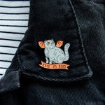 A spooky cat pin on the lapel of a black denim jacket.
