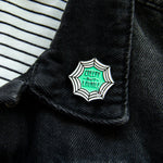 A spiderweb pin on the lapel of a black denim jacket for women.