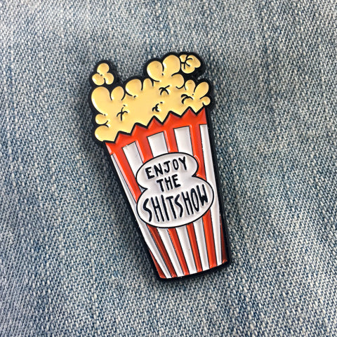 "A funny enamel pin of a bag of popcorn with the quote, ""Enjoy the Shitshow"""