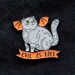 A cute demon cat lapel pin in orange, black, and gray.
