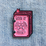 "A creepy cute enamel pin of a witch's grimoire with the title, ""Book of Hexes, Horrors, and Happiness""."