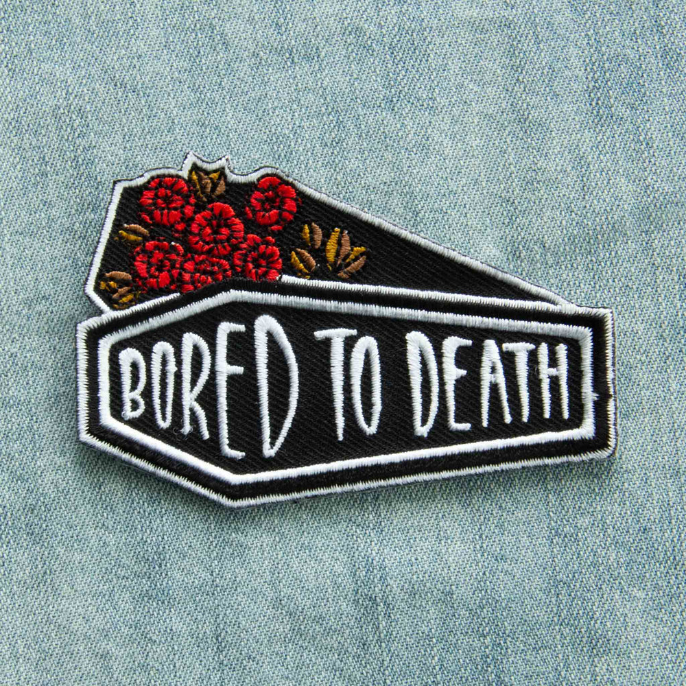 "An iron on embroidered patch with the quote, ""Bored to Death"" on a black coffin with red and gold roses."