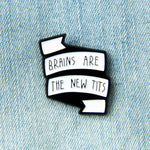 "Feminist banner enamel pin with the quote, ""Brains Are The New Tits""."