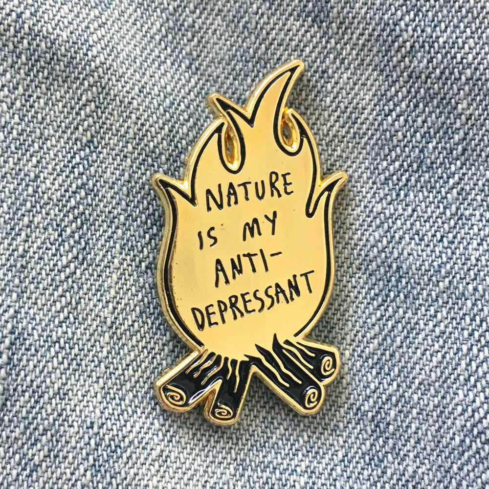 "A gold enamel pin of a campfire with the quote, ""Nature is my Anti-Depressant""."