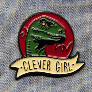 "A Jurassic dinosaur inspired enamel pin of a velociraptor with the quote, ""Clever Girl""."