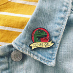 "A unique fandom accessory of an enamel pin that says ""Clever Girl"" on the lapel of a jacket."