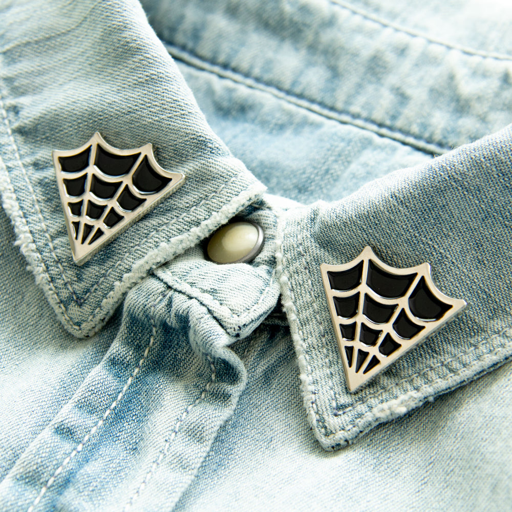 Cool gothabilly cobweb enamel pins for horror fashion.