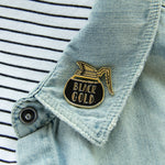 A gold coffee pot brooch on the lapel of a denim jacket for unisex adults.