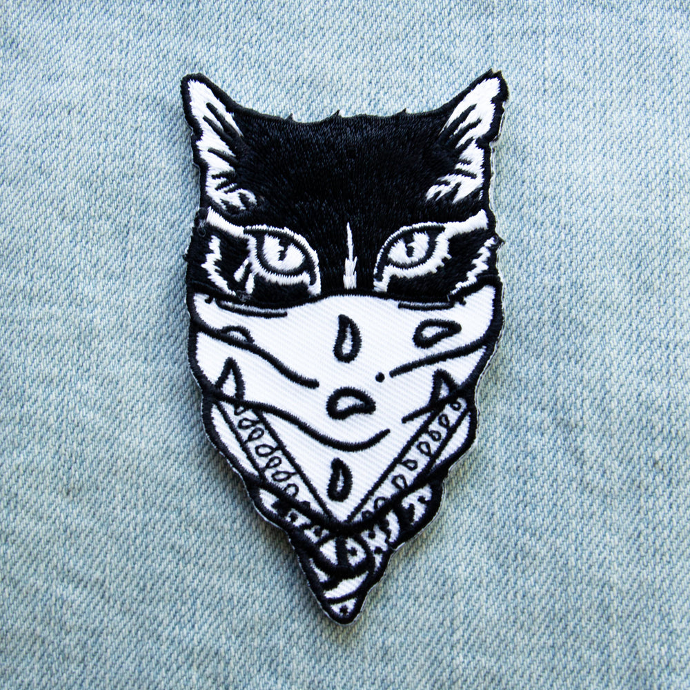 A cool patch of a tattooed gangster cat wearing a bandana over its face. Art designed by Ectogasm.