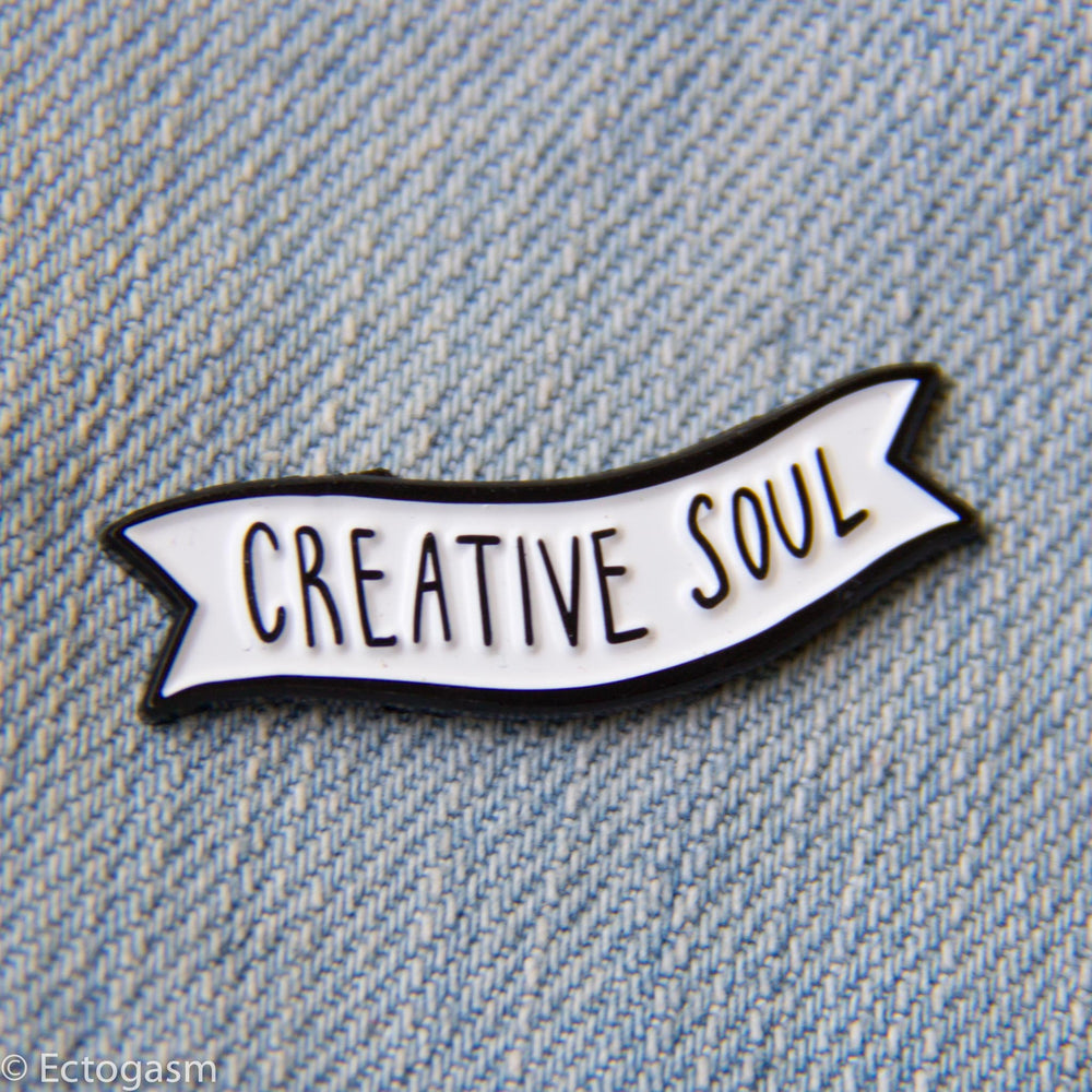 "A cool enamel pin of a black and white banner with the quote, ""Creative Soul""."