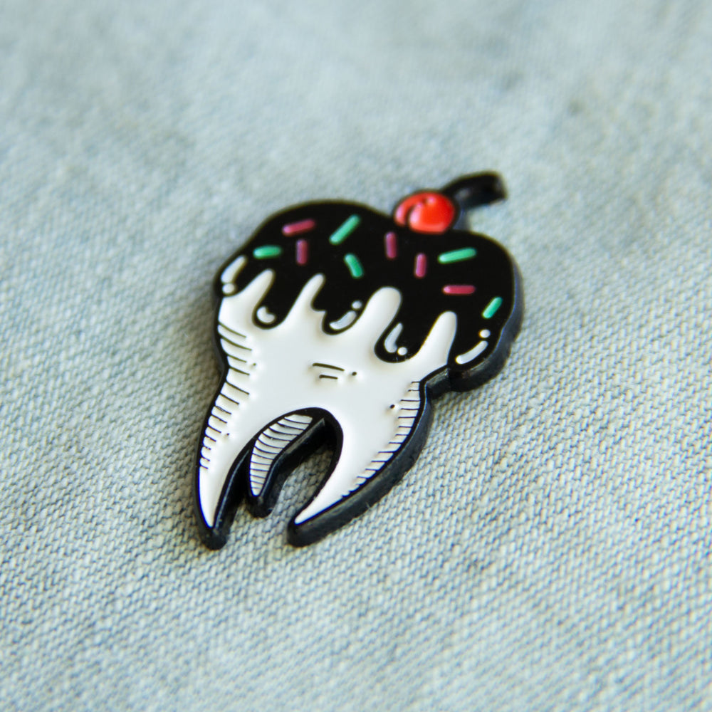 A dessert enamel pin of a sweet tooth.