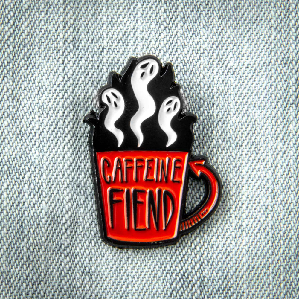"A cool enamel pin of a coffee cup with the quote, ""Caffeine fiend"". Ghosts rise from its brim."