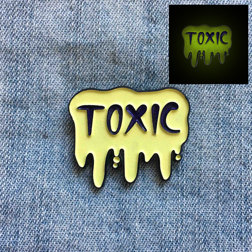 "A glow-in-the-dark enamel pin of the word, ""Toxic"" in dripping slime."