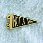 "A funny enamel pin of a sports pennant flag with the quote, ""Not a Fan"". The pin is gold metal with black fill."