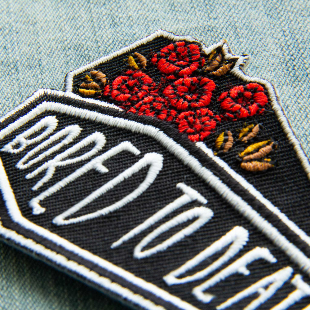 "A witchy iron on patch with the quote, ""Bored to Death"" on a coffin."