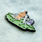 A funny Halloween enamel pin of tombstones with happy skeletons.