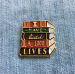 """I Have Lived A Thousand Lives"" book enamel pin in gold."