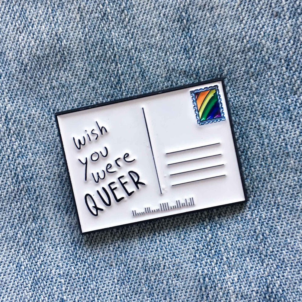 """Wish You Were Queer"" LGBT enamel pin of a postcard with a rainbow stamp."