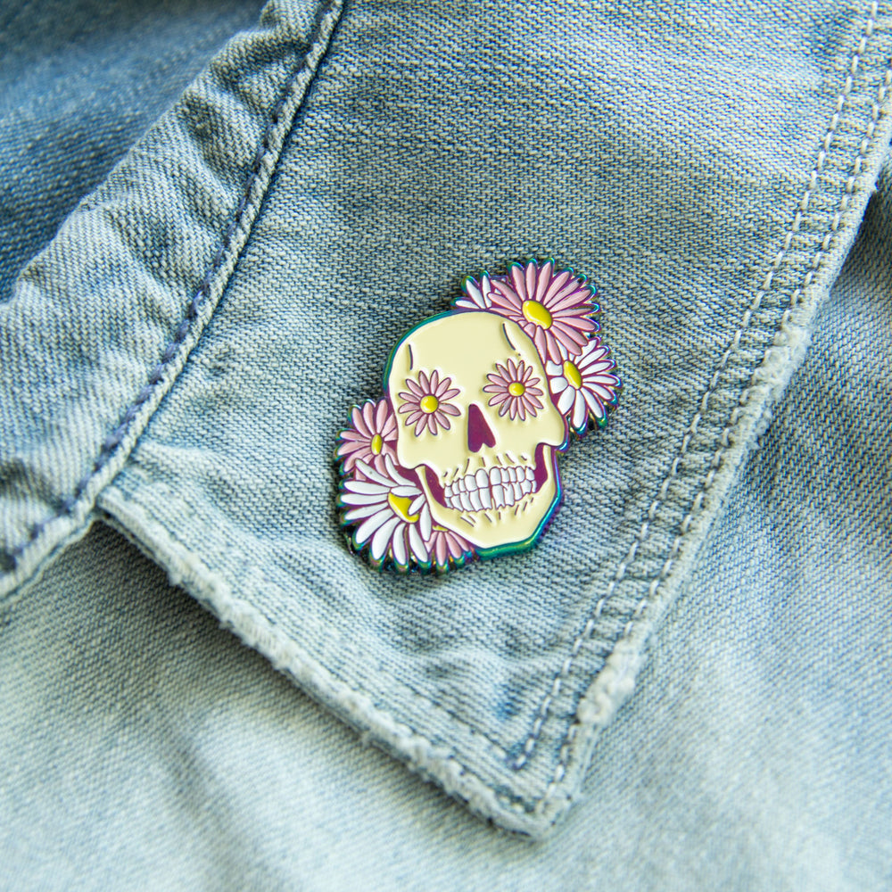 A beautiful sugar skull enamel pin on the lapel of a woman's denim jacket.