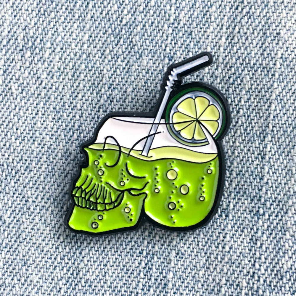 An enamel pin of a lime green cocktail in a glass shaped like a human skull.