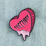 "A spooky enamel pin of a pink candy heart dripping ooze. It has the quote, ""Succubus"" on it."