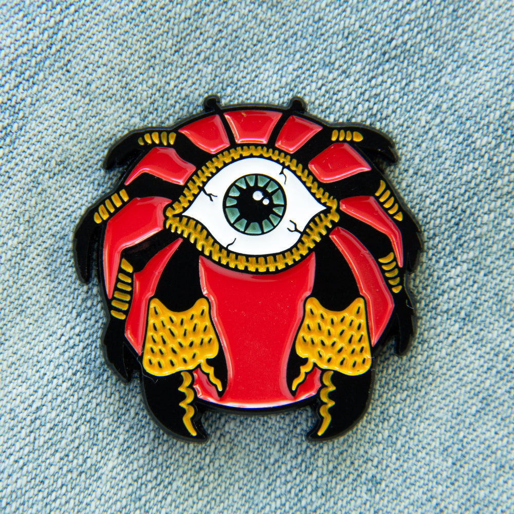 A nautical horror themed enamel pin of a monstrous crab with an eye for its body.