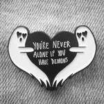 "A funny, gothic enamel pin of two ghosts holding a heart which reads, ""You're Never Alone If You Have Demons."""