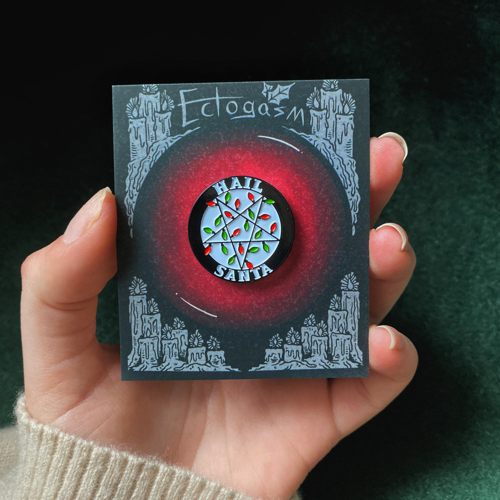 A spooky Christmas enamel pin on an art card.
