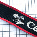 "An enamel pin that says, ""Live in the Moment"" on a camera strap for photographers."