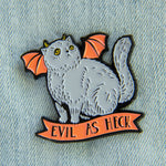 "A cute Halloween enamel pin of a devil cat with horns and batwings. It has the funny quote on it, ""Evil as Heck""."