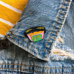 A 90's themed fanny pack enamel pin on the lapel of a denim jacket.