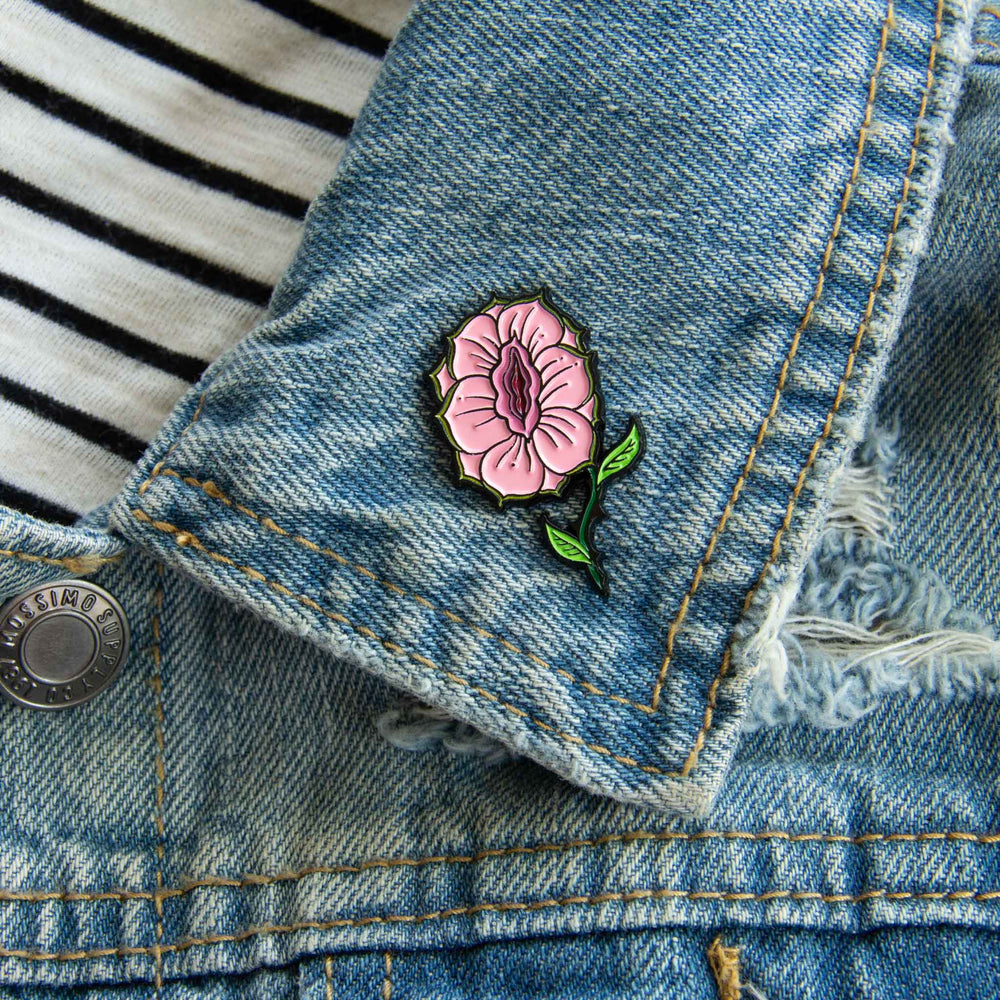 A botanical enamel pin with a hidden vagina center for intersectional feminist fashion.