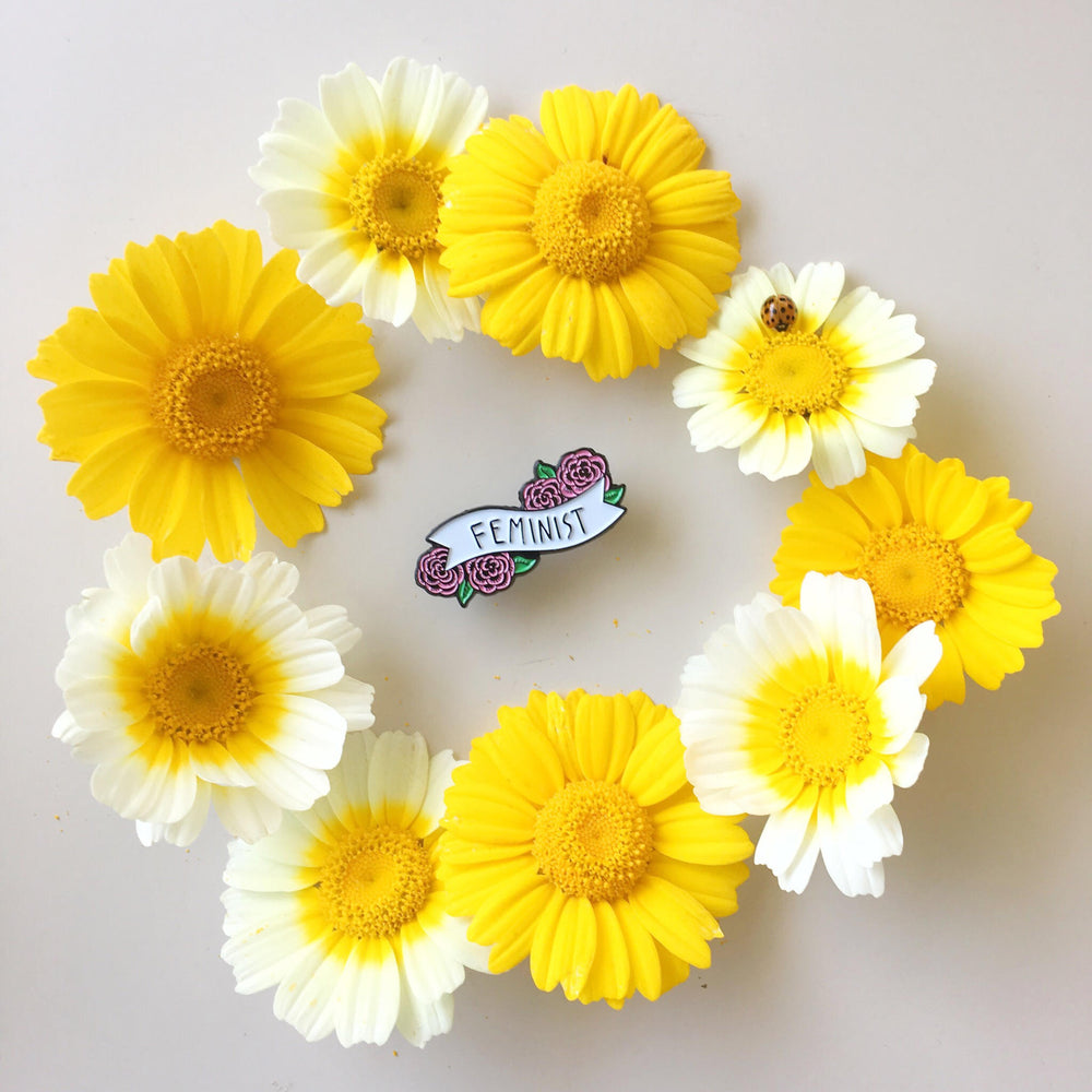 "A cute, flower lapel pin of a banner with the word, ""feminist"" for women's fashion."