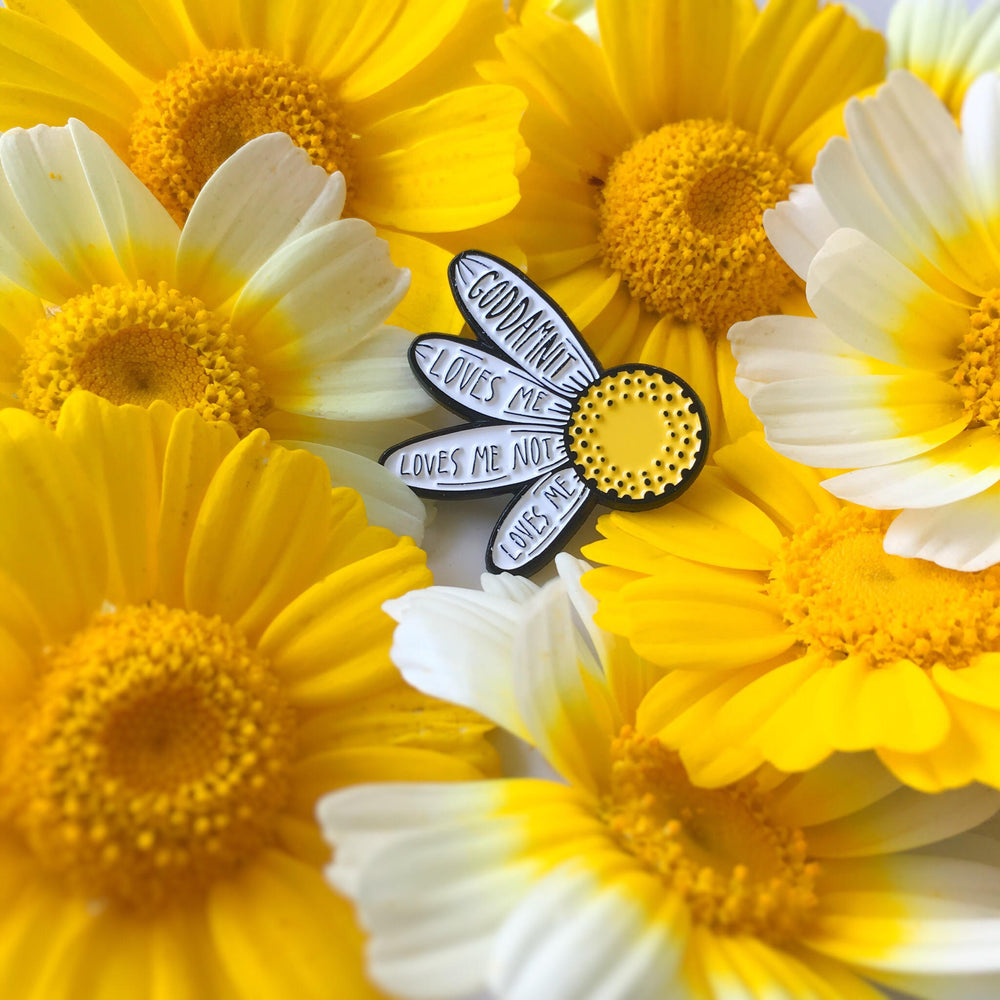 "Ectogasm's ""Loves Me Not"" Flower petal enamel pin on a bed of daisies for cute summery fashion."