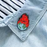 A funny political enamel pin about global warming.