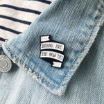 A sassy black and white feminist pin on the lapel of a denim jacket.