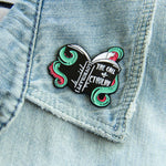 A horror fiction themed enamel pin on the lapel of a jacket for geeky librarian style.