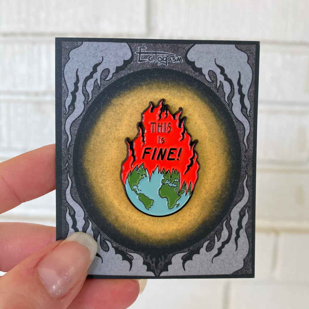 "A funny enamel pin of the world on fire with the sarcastic quote, ""This is fine!"""