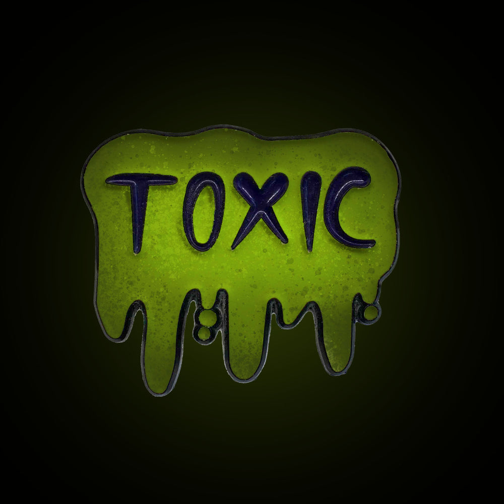 A glow in the dark enamel pin of toxic slime.